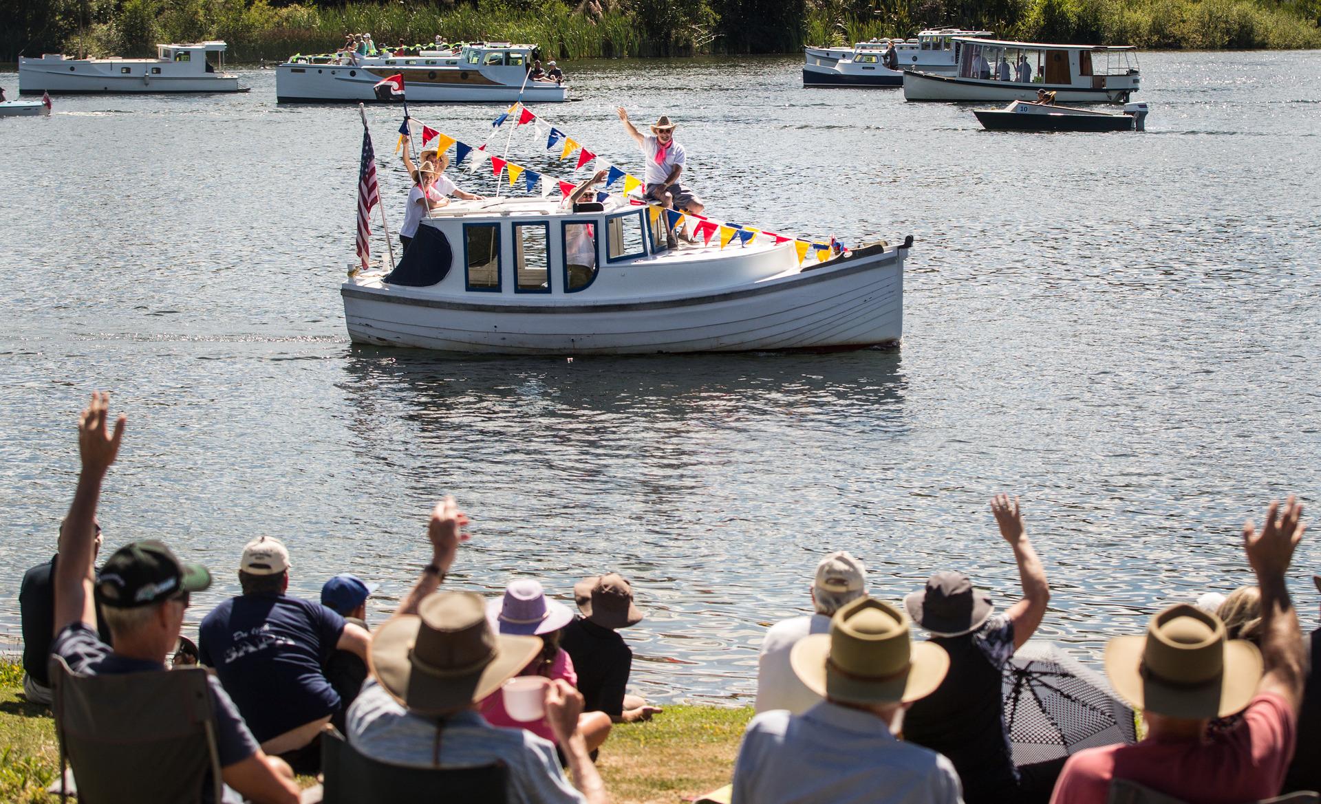Wooden boats parade to isolated bay at Lake Rotoiti, Rotorua