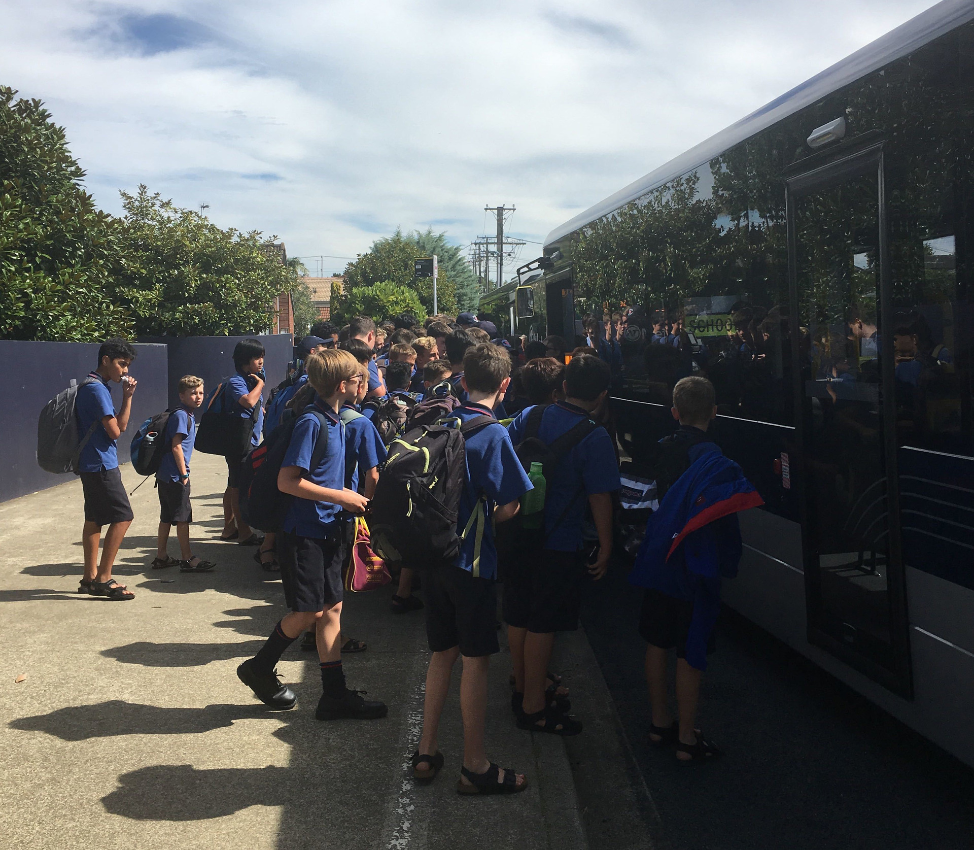Students sitting on knees, standing in door ways on overcrowded buses on Auckland's North Shore